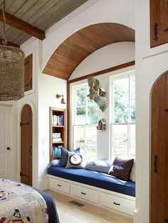 Books are easy to read and easy to put away in this bedroom's clever reading nook. Topped with a thick cushion and pillows, the window seat combines comfort with storage./