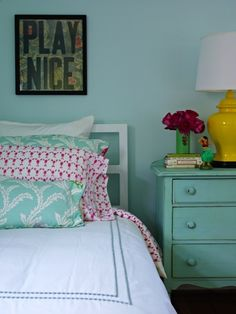 yellow ginger jar lamp turquoise blue walls white bed white hotel bedding blue pearl stitching turquoise blue pillows vintage chest painted turquoise blue green vase art pink pillows