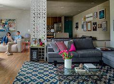 A parede de cobogó da Vianarte cria uma divisória entre os ambientes. Na sala de estar, o sofá em L, da Breton Actual, acomoda a luminária Naja. (Foto: Edu Castello/Editora Globo)
