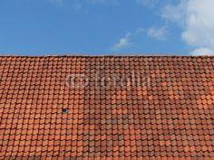 Rotbraunes Ziegeldach vor blauem Himmel mit Wolkenbildung in Oerlinghausen im Teutoburger Wald bei Bielefeld in Ostwestfalen-Lippe