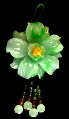 An absolutely wonderful pendant beautifully carved out of a single stone as a flower head and strung with suspended beads and a suspension loop to the