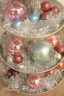 vintage ornaments displayed in tiered stand with silver tinsel garland