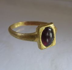 Medieval gold ring ca 1100. The rectangle shaped bezel is set with a cabochon garnet.