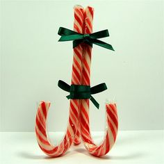 Candy Cane card easel or stand.  Really cute way to display a special Christmas card, photo, or use as a table place card. Use 3 wrapped candy canes, 2 twist ties, and 2 small ribbons to cover the twist ties.  Tie top bow facing the front and the bottom bow facing the back.