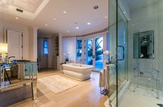 Celine Dion's sprawling bathroom in the songstress's Jupiter Island, Florida mansion has a deep soaking tub at its center and an oversize shower complete with a Kartell Ghost chair.