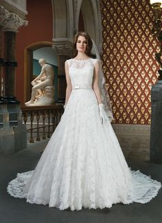 Justin Alexander wedding dresses style 8714 All over Alencon lace circular cut ball gown features a bateau neckline  with cap sleeves. A regal satin fixed double bow wraps around the  natural waist. Regal satin buttons enclose the lace back and continue  until the edge of the train.