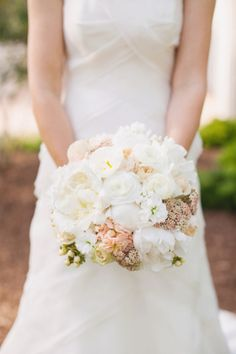 The bridal bouquet was filled with peonies, ranunculus, spray roses, hypernicum, pink stalk, and rice flower.