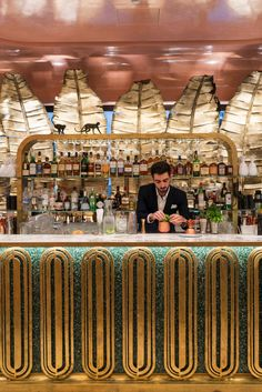 The Flamingo Room's custom designed bar by BASStudio has solid brass details and green terrazzo. The bar is shaded by chiselled brass banana leaves. Monkey sculptures add a playful touch to this African inspired interior.