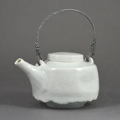 EDMUND DE WAAL (British, b.1964) AR Teapot, 1995 Porcelain, pale blue celadon glaze with a delicate crackle, mounted with a twisted looping g silver metal handle, impressed maker's mark