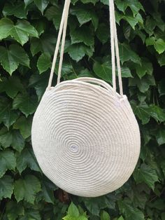 Round purse made out of coiled natural cotton rope with shoulder strap and top handles. The neutral soft white brightens every outfit--I get compliments on my bag every time I wear it! This bag is durable and roomy enough to fit all your necessities - measures about 12 inches across and 2 inches deep, with about small top handles and a 30 inch long shoulder strap. The cotton rope has polyester threads hidden in the center to prevent stretching and to make it lighter. The rope is sewn into…