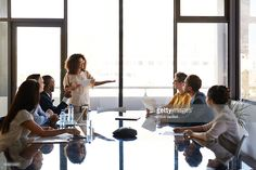 Businesswoman doing presentation in conference room with big glass table