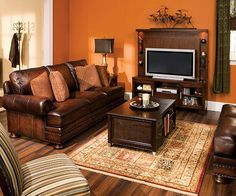 Walnut leather and warm-hued accent pillows take center stage in a traditionally styled room. Pick a warm orange that matches the tones in the pillows and pair with dark wood tables with ring pulls to carry the classic theme throughout the room.