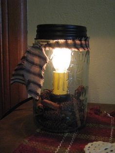 This pale green glass Pint Mason Jar Candle Lamp has an electric candle inside with cinnamon sticks and baby birch cones.Shop Primitive Star Quilt Shop now. https://www.primitivestarquiltshop.com/collections/sconces-lighting/products/pint-mason-jar-candle-lamp #primitivehomedecor