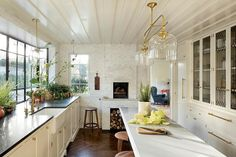 Charming kitchen space with white shaker cabinets and a marble tiled fireplace | Jessica Helgerson Interior Design