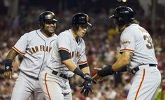 San Francisco Giants' Joe Panik, center, is congratulated by teammates Pablo Sandoval, left, and Michael Morse after hitting a three-run hom...