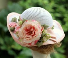 A delightful garden party wide brim summer hat in white straw for a romantic shabbye chic look. The hat has a pleated pale dusty pink pleated band accented with a narrow band of tiny hombre roses. The hat is decorated in a large lifelike hombre fu...