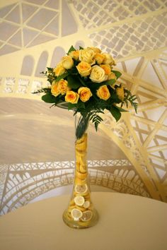 great flower arrangement idea--yellow roses and lemons (seen at an event in Cali.)