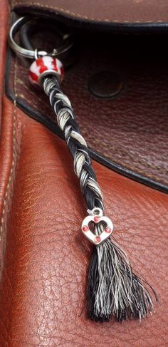 "The ""Anna"" style keychain features a regular 3-strand braid with a glass bead or jewel bead on top and accented with a charm at the bottom of the braid."