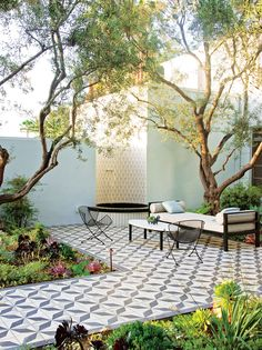 STUNNING!    Beneath the olive trees, a Heath Ceramics-tiled water feature with Plain Air furniture and striking encaustic Granada Tile underfoot. PHOTO:...