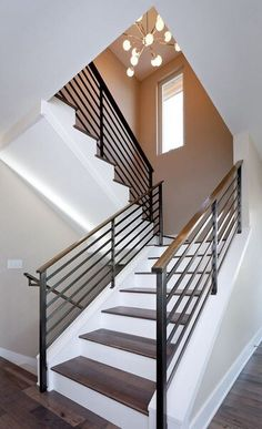 A simple and stylish way to make the staircase look simple yet chic and eye-catching is to use contrasts. In this case, for example, the wooden stairs sit on a crisp white background and the metal guardrail with wooden handrail frame them beautifully. Indoor Railing, Modern Stair Railing, Wrought Iron Stair Railing, Stair Railing Design, Metal Stairs, Metal Railings, Staircase Railings, Banisters, Railing Ideas