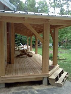 This custom designed and crafted timber frame farmers porch adds to a beautiful backyard setting providing covered dining and entertaining space.