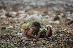 A girl plays with her brother as they search for usable items at junkyard near the Danyingone station in Yangon's suburbs May 16, 2012. REUTERS-Damir Sagolj