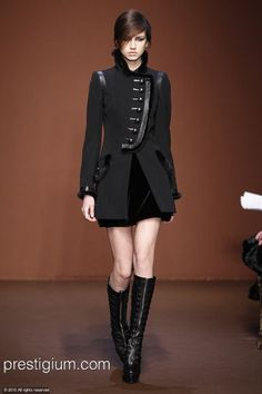 High-collared asymmetrical coat with mink and leather trim, metal buttons.