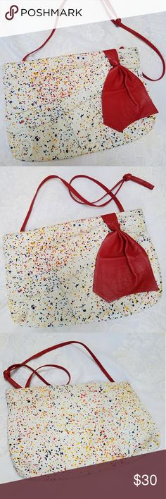 VTG Leather Paint Spatter Bag with Red Bow Unusual shoulder bag, in white leather with cherry red strap and bow, and paint spatter design in primary colors. Rigid top frame snaps open and closed, and has a small zip packet inside. In great condition! Made in Colombia. Measures 14 x 9.5 inches. Vintage Bags Shoulder Bags