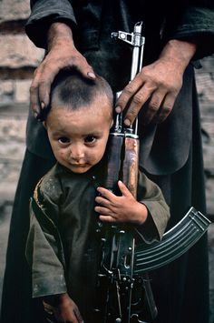A young boy stands next to his father's AK-47. Kabul, Afghanistan, 1992. By Steve McCurry.