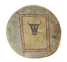 Plains Pictorial Painted Hide Shield composed of finely tanned hide stretched around a circular wood hoop and secured on the reverse withdrawstring construction, painted on thefront with a concentric rectangle in red and black pigments, enclosing a stylized buffalo head against a yellow ground. diameter 16 1/4 in. Cf. Mauer, 1993, p. 38 for a similar shield identified as Teton Lakota from the collection of the NMAI, Smithsonian Institution.  Sotheby's. AMERICAN INDIAN ART 8 May 2006. NY.
