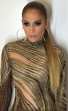 Who made Jennifer Lopez's black mesh strip dress, gold jewelry, and triple strap sandals?