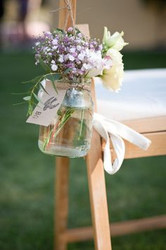 either jars of lavender, or just little bouquets of lavender on the chairs.  And, if you add a flower to the centerpieces, you could add them to these, too.  Even has the burlap string already.