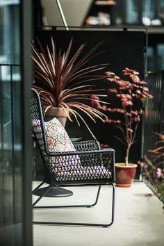 Small apartment balcony with minimalistic outdoor interior in black and red tones.