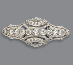 DIAMOND AND SAPPHIRE BROOCH, CIRCA 1925. The shaped openwork plaque set with 52 round and single-cut diamonds weighing approximately 4.50 carats and accented with bands of French calibré-cut sapphires, mounted in platinum.