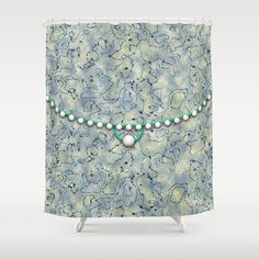 This original abstract design is a pattern of squiggles in dark blue on a textured background of smokey colors, aquas, light blues and pale yellows. The design is in the style of a clutch bag, with an oval flap trimmed in an aqua band and bordered with pearls. At the center of the purse is the flap closure, with an aqua band finished with a larger pearl.