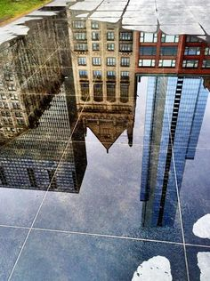 Puddles reflect buildings around Millennium Park in Chicago