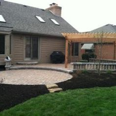 This winning combination features a step down bi-level curved paver patio, curved seating wall and cedar pergola.