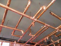 Stand del Birrificio Poretti: guarda l'intreccio di tubi sul soffitto: è il sistema di illuminazione!