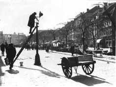 Een lantaarnopsteker pleegt onderhoud aan een straatlantaarn  in de Boschstraat in Maastricht.