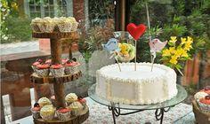 Mesa de bolo de casamento ao ar livre com o bolo branco de pasta americana
