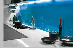 Just one simple coloured glass splashback against plain counters can completely transform your #kitchen. View more kitchen splashbacks and non-scratch glass worktops on http://www.creoglass.co.uk/kitchen-glass-splashbacks/