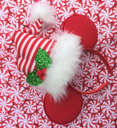 These Holiday Elf Mickey/Minnie ears are plush and full of Holiday cheer. Ears are covered in a bright red felt with fuzzy edges just like Mickey and Minnies and a plush stuffed Elf hat sits on top complete with fur lining and ball and a glittery tinsel fabric holly with velvet