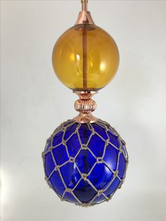 Glass and Macrame ball light features in amber and cobalt blue made by Rothschild & Bickers for Ted Baker store in Vancouver