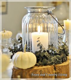 Fall centerpiece using wood slice as the base for candle in a large glass jar circled with eucalyptus at the base.