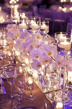 A mirrored runner overflows with arrangements of white orchids and floating candles.
