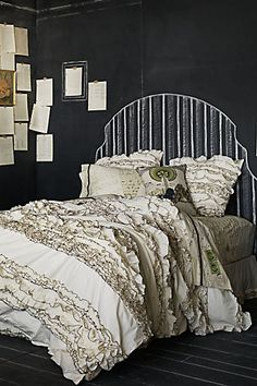love the girly ruffles against the chalkboard walls and headboard, especially love the sheets with love letters on them :)
