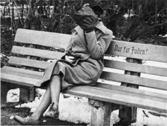 """A Jewish woman who is concealing her face sits on a park bench marked """"Only for Jews"""", Austria, 1938"""