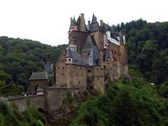 Burg Eltz is a medieval castle nestled in the hills above the Moselle River between Koblenz and Trier, Germany. It is still owned by a branch of the same family that lived there in the 12th century, 33 generations ago.  The castle is a so-called Ganerbenburg, or castle belonging to a community of joint heirs. Burg Eltz is surrounded on three sides by the Elzbach River, a tributary on the north side of the Moselle.