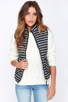 "The next time you hit the slopes (or the lodge) puffer up in the Dee Elle Aspen Navy Blue and Ivory Striped Puffer Vest! This quilted navy blue vest is perfectly padded for added warmth, boasting fun ivory stripes that run from the mock neck down into the sleeveless bodice in a sleek woven material. A shiny gold zipper closure runs the length at front, while gold snap buttons secure the two front flap pockets. Fully lined. Top measures 2"" longer at back. 100% Polyester. Dry Clean Only. ..."