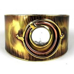 Dramatic rings of copper and brass surround a howlite stone in this brass cuff made by South African artisans. The coloration of the brass is achieved by applying high heat rather than paints or dyes.Bracelet dimensions: 40 mm wide x 7 inches long. Copper Cuff, Copper And Brass, Solid Brass, Artisan Jewelry, Handcrafted Jewelry, Bracelet Display, Cuff Bracelets, Bangles, Fair Trade